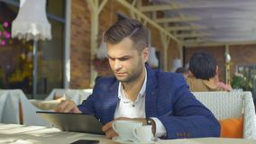 Using the Tablet in Cafe. A man sits at a table in a cafe and use your tablet stock footage