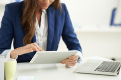 Using tablet computer. Modern business: manager using tablet computer her workplace Royalty Free Stock Photo