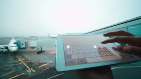 Using tablet computer by the window at airport. Close-up shot of woman typing message on touch pad on background of boarding plane at airport stock video footage