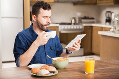 Using a tablet and eating breakfast Stock Images