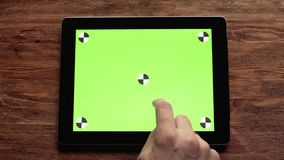Using tablet with green screen on wooden table. Great for mock-up usage. Shot in 4K, UHD stock video footage