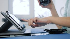 Using tablet during morning coffee in woman`s hand on unfocused background. Using tablet during morning coffee in woman`s hand close-up on unfocused background stock footage