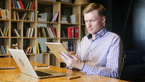 Using Tablet in Office. Using tablet pc, young man , freelancer stock footage