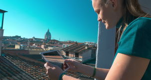 Using tablet on outdoor balcony of old house. Steadicam shot of a woman working with tablet computer standing on the balcony with great city view stock video footage