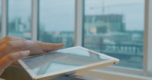 Using tablet PC for chat messaging. Close-up shot of female hand typing a chat message on touchscreen by the window. Defocused city view in background stock video footage