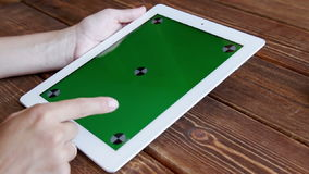 Using tablet pc touchscreen. Using tablet pc with green screen on wooden desk stock video