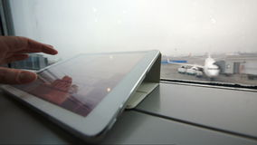 Using tablet PC on windowsill at the airport. Close-up shot of a female hand typing on tablet computer by the window at airport on background of boarding plane stock video footage