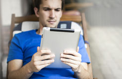 Using Tablet. Young man using his tablet PC royalty free stock photography
