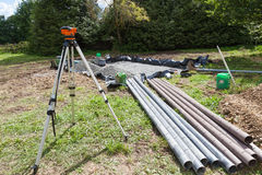 Using a theodolite to instal a gravel filter bed on a septic tank. Using a theodolite to instal a gravel filter bed for a household septic tank showing the royalty free stock photo