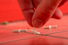 Using Tile Spacers on Red Tiles. Close Up of Hand Using Tile Spacers in Preparation for Grouting on Red Tiles Stock Photography