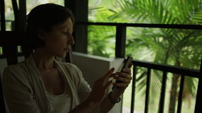 Using touch screen mobile phone. Smiling woman use touch screen mobile phone sitting on the balcony stock video