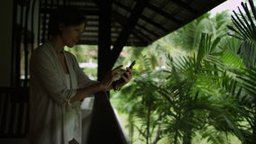 Using touch screen mobile phone. Smiling woman use touch screen mobile phone standing on the balcony stock footage