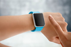 Using Touch Screen Smart Watch. Women Using Touch Screen Smart Watch with Blue Strap Stock Photos