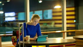Using a touchpad in the airport terminal. Young woman having coffee and using a tablet PC in the airport terminal stock footage