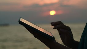 Using touchpad on the beach at sunset. Close-up shot of woman using tablet computer outdoor. Sunset over the sea in background stock video footage
