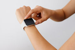 Using touchscreen smart watch Isolated. Using touchscreen smart watch with white strap Royalty Free Stock Images