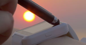 Using touchscreen smartwatch at sunset. Close-up shot of a woman using smartwatch with a pen. Sunset scene in background. Modern gadgets for convenient life stock video footage