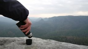 Using of travel thermos on the rocks. Vacuum bottle with smoking cup with tea. Using of travel thermos on the rocks. Vacuum bottle with smoking black cup with stock video footage