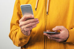 Using two mobile phones for communication. Man using two mobile phones for SMS communication, male person wearing yellow shirt with zipper sending text messages Royalty Free Stock Images