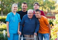 Using the walker. Family visiting grandfather at the nursing home, helping him with the walker Royalty Free Stock Image