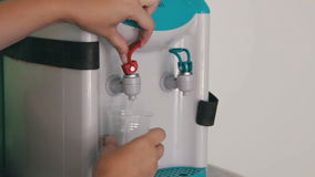 Using Water Dispenser. Filling Cup At Water Cooler, Water Dispenser. Using Water Dispenser. Woman filling cup at water cooler, water dispenser. Full HD 1920 x stock video footage