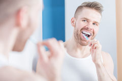 Using whitening toothpaste. Man with toothbrush using whitening toothpaste Stock Images