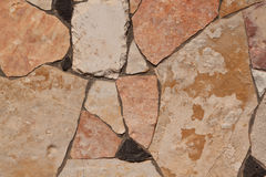 Using wild stone in construction. Untreated natural stone deposited on the wall Royalty Free Stock Image