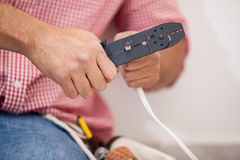 Using a wire stripper. Closeup of a man using a wire stripper at home Royalty Free Stock Image