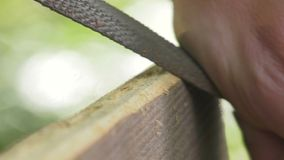 Using a wood rasp on the edge of a board. Woodworking rasp creates a bevel on the board angle stock video footage