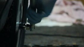 Using wrench on tire. Tightening nuts on tire in garage stock footage
