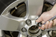 Using a wrench to tighten the nuts on a tire Royalty Free Stock Photography