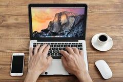 Uso Apple MacBook Pro degli uomini Fotografia Stock Libera da Diritti