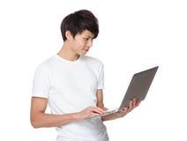 Uso asiatico del giovane del computer portatile Fotografie Stock