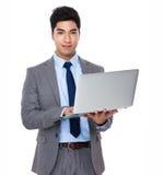 Uso asiatico dell'uomo d'affari del computer portatile Fotografia Stock