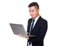 Uso asiatico dell'uomo d'affari del computer portatile Immagini Stock