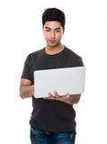Uso asiatico dell'uomo del computer portatile Fotografia Stock Libera da Diritti