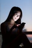 Uso asiatico della donna del cellulare a casa Fotografia Stock