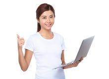 Uso asiatico della donna del computer portatile e del pollice su Fotografie Stock