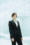 Uso asiatico femminile attraente della donna di affari cuffie con il microfono Fotografie Stock Libere da Diritti