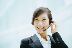 Uso asiatico femminile attraente della donna di affari cuffie con il microfono Fotografie Stock