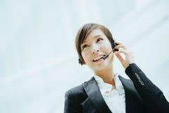 Uso asiatico femminile attraente della donna di affari cuffie con il microfono Fotografia Stock