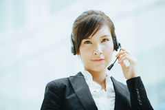 Uso asiatico femminile attraente della donna di affari cuffie con il microfono Fotografia Stock Libera da Diritti