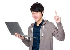 Uso bello asiatico dell'uomo del computer portatile e del dito su Immagini Stock Libere da Diritti