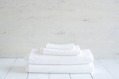 Uso blanco de las toallas del algodón en cuarto de baño del balneario en el fondo de madera fotos de archivo libres de regalías