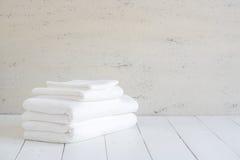 Uso blanco de las toallas del algodón en cuarto de baño del balneario en el fondo de madera Fotografía de archivo
