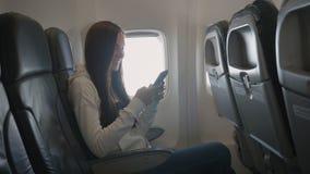 Uso bonito da menina do telefone celular dentro do avião vídeos de arquivo