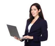 Uso castana della donna di affari del computer portatile Fotografia Stock