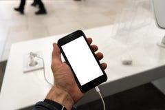 Uso da vida real do telefone em uma mão dos homens que guarda com espaço da cópia gratuita para seus anúncio e texto - trocistas  imagem de stock