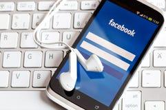 Uso de Facebook en la pantalla elegante del teléfono. foto de archivo