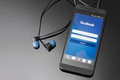 Uso de Facebook en la pantalla elegante del teléfono. fotografía de archivo